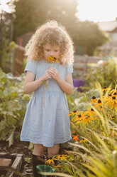 Little girl smelling flowers in the garden - NMSF00161