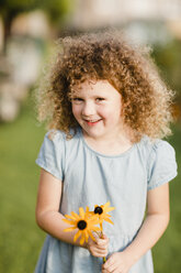 Portrait of happy little girl with picked flowers in the garden - NMSF00164