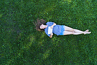 Young woman lying on grass, holding digital tablet - MAEF12418