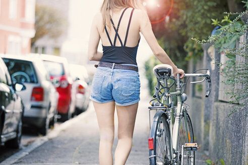 Young woan with bicycle in the city - MAEF12424