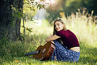 Young woman sitting on meadow, playing guitar - MAEF12427