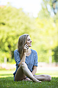 Young woman  sitting on grass talking on the phone - MAEF12430