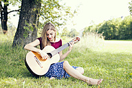 Young woman sitting on meadow, playing guitar - MAEF12442