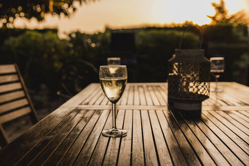 Glass of white wine on table at sunset - NMSF00176