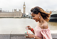 UK, London, happy woman making soap bubbles near Westminster Bridge - MGOF03629
