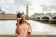 UK, London, beautiful woman taking a picture near Westminster Bridge - MGOF03641
