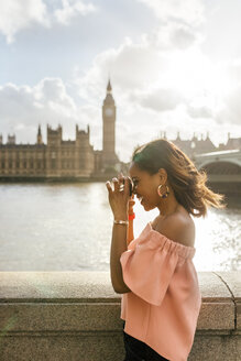 UK, London, beautiful woman taking a picture near Westminster Bridge - MGOF03644