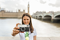 UK, London, woman holding old-fashioned camera near Westminster Bridge - MGOF03647