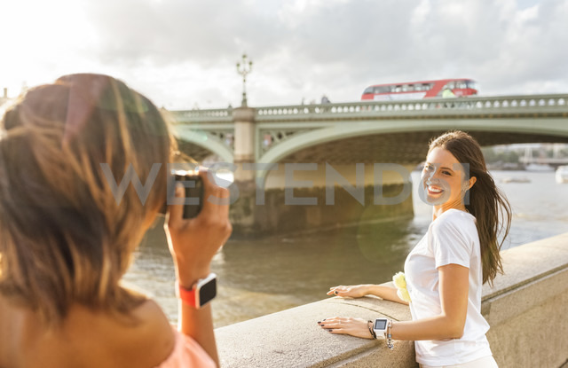 UK, London, woman taking a picture of her friend near Westminster Bridge - MGOF03650 - Marco Govel/Westend61