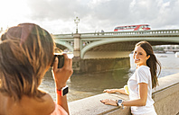UK, London, woman taking a picture of her friend near Westminster Bridge - MGOF03650
