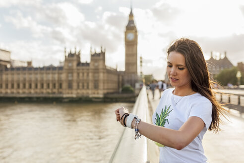 UK, London, oman using her smartwatch on Westminster Bridge - MGOF03653