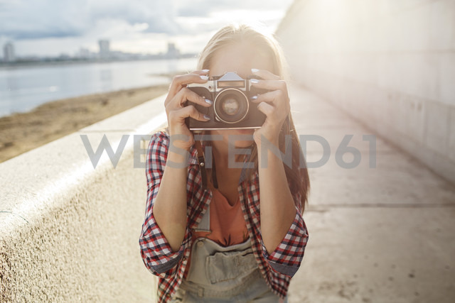 Young woman taking a picture with a camera at the riverside - VPIF00159