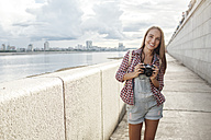 Smiling young woman with a camera at the riverside - VPIF00162