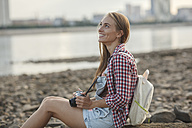 Smiling young woman with a camera sitting on stony beach - VPIF00165