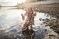 Happy young woman spalshing in a river at sunset - VPIF00177