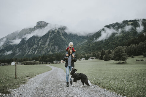 Austria, Vorarlberg, Mellau, mother carrying toddler on shoulders on a trip in the mountains - DWF00317