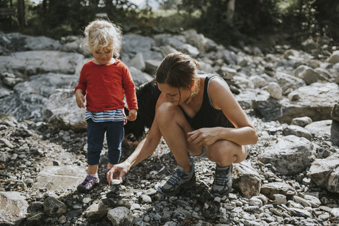 Mother and toddler building a heap of stones - DWF00320