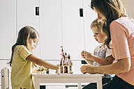 Mother with two children building up toy castle at home - JUBF00255