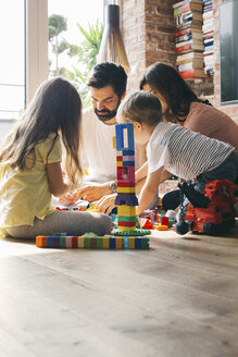 Family playing with building blocks on the floor together - JUBF00258