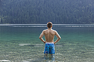 Germany, Bavaria, Eibsee, back view of young man standing in water - TCF05446