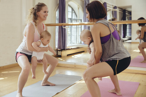 Two mothers working out on yoga mats with babies in their arms - MFF03998