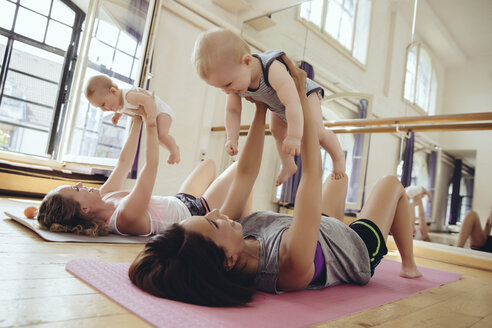 Two mothers working out on yoga mats while holding up their babies - MFF04001