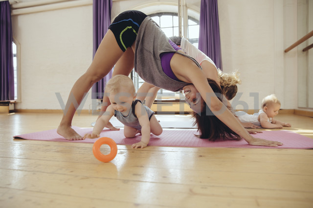 Two mothers working out on yoga mats with babies playing around them - MFF04004