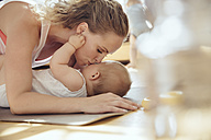 Mother kissing her baby while working out on a yoga mat - MFF04007