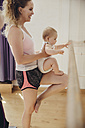 Two mothers holding up their small children to barre in dance studio - MFF04016