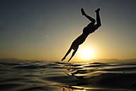 Man jumping into the sea at sunset - ECPF00134