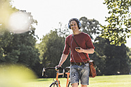 Smiling man with racing cycle listening music with headphones in a park - UUF11739
