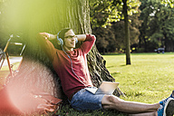 Man with laptop and headphones relaxing in park - UUF11751