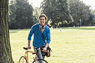 Portrait of relaxed man with racing cycle in a park - UUF11754