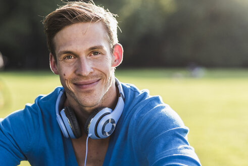 Portrait of smiling man with headphones in a park - UUF11760