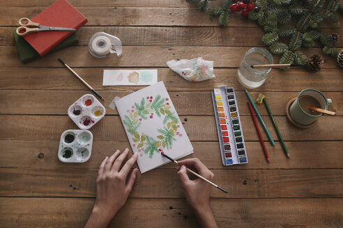 Young woman painting Christmas card with water colors, top view - RTBF01017