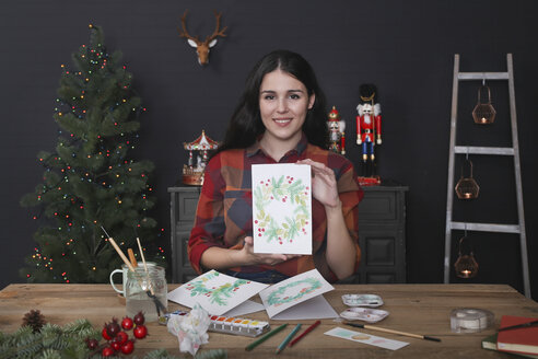 Portrait of smiling young woman showing her painted Christmas card - RTBF01020