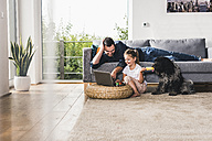 Father using laptop at home with his little daughter - UUF11776