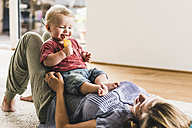 Mother and son at home eating ice lolly - UUF11788