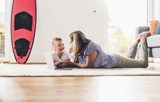 Mother and daughter using laptop, lying on carpet - UUF11800
