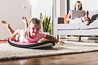 Little girl playing on surfboard in living room - UUF11803