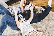 Family using VR goggles at home - UUF11812