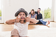 Little girl with hat having fun at home, parents using laptop in background - UUF11815