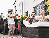 Fathercand daughter in the garden, daughter splashing water with hose - UUF11830