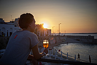 Italy, Santa Maria al Bagno, woman relaxing with glass of Spritz at sunset - DIKF00269