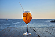 Glass of ice-cooled Spritz with orange slice in front of the sea - DIKF00272