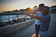 Italy, Santa Caterina, grandfather and grandson looking at view by sunset - DIKF00275