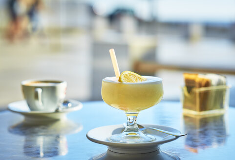 Italy, glass of lemon granita and cup of Cappuccino in the background - DIKF00278