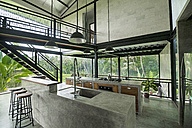 Modern minimalist kitchen in contemporary design house with glass facade surrounded by lush tropical garden - SBOF00794