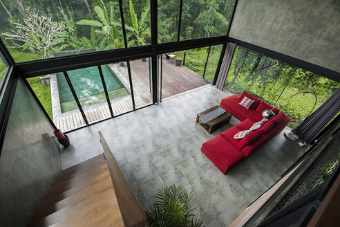 Modern minimalist living room with red couch in contemporary design house with glass facade surrounded by lush tropical garden with pool - SBOF00797