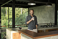 Handsome man drinking coffee in modern design kitchen with glass facade surrounded by lush tropical garden - SBOF00800